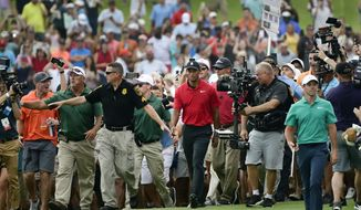 FILE - In this Sept. 23, 2018, file photo, Tiger Woods, center, and Rory McIlroy, right, make their way down the 18th fairway during the final round of the Tour Championship golf tournament in Atlanta. Woods won the Tour Championship for his 80th career PGA Tour victory, all the evidence he needs for high expectations. He's also wise enough to know his expectations won't be as high as they once were because of age. (AP Photo/John Amis)