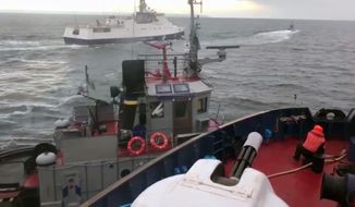 In this image taken from video released by the Russia's Federal Security Service taken from a Russian Coast Guard vessel purporting to show an incident between the Russian coast guard and a Ukrainian tugboat, in the Kerch Strait on Sunday Nov. 25, 2018. Russia said three Ukrainian vessels made an unauthorised passage through Russian territorial waters, while Ukraine alleged that one of its boats was rammed by a Russian coast guard vessel. (Russia's Federal Security Service via AP)