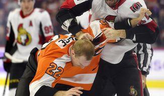 Ottawa Senators' Ben Harpur, top, fights Philadelphia Flyers' Dale Weise (22) during the first period of an NHL hockey game Tuesday, Nov. 27, 2018, in Philadelphia. (AP Photo/Derik Hamilton)