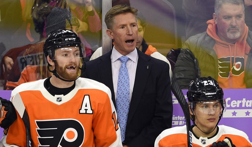 Philadelphia Flyers coach Dave Hakstol, center, calls out to his team during the first period of an NHL hockey game against the Ottawa Senators, Tuesday, Nov. 27, 2018, in Philadelphia. The Senators won 4-3. (AP Photo/Derik Hamilton)