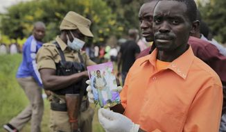 FILE - In this Thursday, Dec. 1, 2016 file photo, a man holds a photograph of his relative as he waits in a line to identify bodies from the fighting the previous weekend, some heavily burned, at the mortuary in Kasese, Uganda. On Nov. 27, 2018 the United States are urging that Ugandan authorities fully investigate a military attack on a tribal king's palace two years ago that killed over 100 civilians. (AP Photo/Arne Gillis, File)