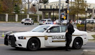 Montgomery police block the entrance of Walter Reed National MilitaryMedical Center Tuesday, Nov. 27, 2018, in Bethesda Md. The Navy says a drill was taking place at the Maryland base that's home to Walter Reed where an active shooter had been reported. Naval Support Activity Bethesda tweeted that no shooter had been found and personnel could move about the Maryland base freely. (AP Photo/Jose Luis Magana)