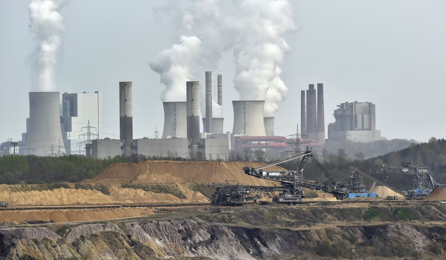 In this April 3, 2014, file photo giant machines dig for brown coal at the open-cast mining Garzweiler in front of a smoking power plant near the city of Grevenbroich in western Germany. Despite uncertainties about whether the United States will remain committed to the Paris climate accord under President Donald Trump, diplomats convened talks in Bonn, Germany, Monday, May 8, 2017 on implementing the details of the global deal to combat global warming. (AP Photo/Martin Meissner, File)