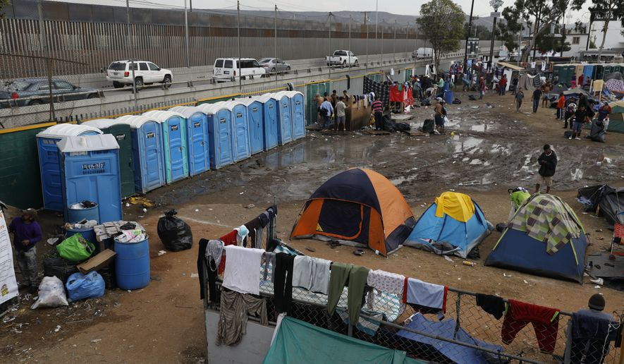 People walk through a muddy section inside an overflowing sports complex where more than 5,000 Central American migrants are sheltering in Tijuana, Mexico, Wednesday, Nov. 28, 2018. As Mexico wrestles with what to do with the thousands of people camped out in the border city of Tijuana, President-elect Andres Manuel Lopez Obrador's government signaled Tuesday that it would be willing to house the migrants on Mexican soil while they apply for asylum in the United States, a key demand of U.S. President Donald Trump. (AP Photo/Rebecca Blackwell)