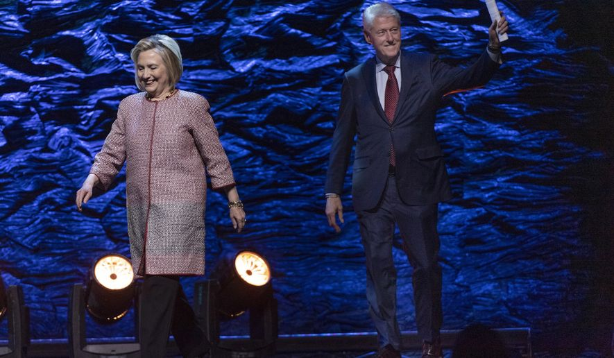 Former U.S. President Bill Clinton, right, and former Secretary of State Hillary Rodham Clinton walk onstage for a conference in Montreal on Wednesday, Nov. 28, 2018. (Paul Chiasson/The Canadian Press via AP)
