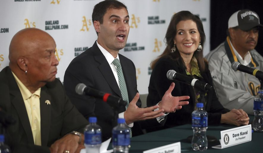 Oakland Athletics President Dave Kaval, second from left, gestures beside Oakland Mayor Libby Schaaf during a media conference Wednesday, Nov. 28, 2018, in Oakland, Calif. The Oakland Athletics have found a location for their modern new ballpark, announcing plans to build near Jack London Square along the water. At left is President of the Board of Port Commissioners Ces Butner, Oakland City Council President Larry Reid is seen at right. (AP Photo/Ben Margot)