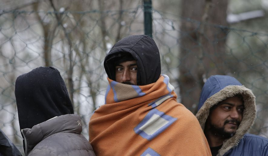 Migrants wait for food distribution in Bihac, Bosnia, close to the border to Croatia on Wednesday, Nov. 28, 2018. The approach of the tough Balkan winter spells tough times for the migrants that remain stuck in the region while trying to reach Western Europe, with hundreds of them staying in make-shift camps with no heating or facilities. (AP Photo/Amel Emric)