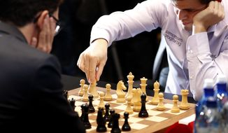 Reigning chess world champion, Norway's Magnus Carlsen, makes a move whilst playing against Italian-American Fabiano Caruana at the final day of the World chess Championship in London, Wednesday, Nov. 28, 2018.(AP Photo/Frank Augstein)