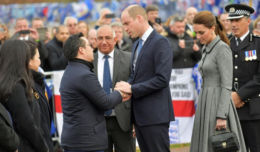 Leicester City Vice chairman Aiyawatt Srivaddhanaprabha, the son of deceased owner Vichai Srivaddhanaprabha, left, shakes hands and talks with Britain's Prince William and Kate, Duchess The Duke of Cambridge, as they view tributes to those who were killed in an helicopter crash at Leicester City Football Club's King Power Stadium in Leicester, England, Wednesday, Nov. 28, 2018. Vichai Srivaddhanaprabha, the Thai billionaire owner of Premier League team Leicester City was among five people who died after his helicopter crashed and burst into flames shortly after taking off from the soccer field on Saturday Oct. 27, 2018. (AP Photo/Arthur Edwards)