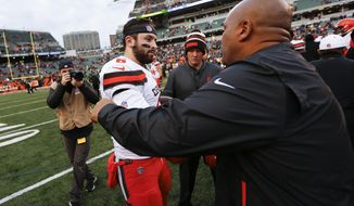 """FILE - In this Sunday, Nov. 25, 2018, file photo, Cleveland Browns quarterback Baker Mayfield (6) meets with Cincinnati Bengals special assistant Hue Jackson, right, after an NFL football game in Cincinnati. Mayfield said he doesn't regret calling former Browns coach Hue Jackson """"fake"""" and said he has no plans to change despite criticism about his behavior.(AP Photo/Frank Victores, File)"""