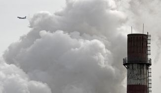 In this file photo taken Tuesday, Feb. 28, 2017, a passenger airliner flies past steam and white smoke emitted from China Huaneng Group's Beijing power plant that was the last coal-fired plant to shut down on March 18, 2017, as the Chinese capital convert to clean energy like thermal power. (AP Photo/Andy Wong, File)