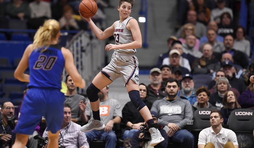 Connecticut's Katie Lou Samuelson leaps to keep a ball in play as DePaul guard Kelly Campbell (20) looks on during the first half of an NCAA college basketball game in Hartford, Conn., Wednesday, Nov. 28, 2018. (AP Photo/Jessica Hill)