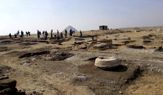 This undated photo released by the Egyptian Ministry of Antiquities on Wednesday, Nov. 28, 2018, shows archaeologists standing near an ancient mummy which was found inside a sarcophagus in area of King Amenemhat II's pyramid in the Dahshur royal necropolis, about 25 miles south of Cairo. Egypt says archaeologists have discovered eight limestone sarcophagi with mummies inside. (Egyptian Ministry of Antiquities via AP)