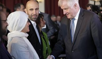 German Interior Minister Horst Seehofer, right, shakes hands with a participant as he arrives for the 4th German Islam Conference in Berlin, Germany, Wednesday, Nov. 28, 2018. (AP Photo/Michael Sohn)