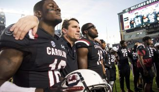 FILE - In this Saturday, Oct. 13, 2018, file photo, South Carolina head coach Will Muschamp, second from left, puts his arms around Rashad Fenton (16) and Aaron Sterling (15) after an NCAA college football game against Texas A&M in Columbia, S.C. Hurricane Florence and the looming bowl season has South Carolina and Virginia Tech closing their football seasons against teams that were never on their schedule. (AP Photo/Sean Rayford, File)