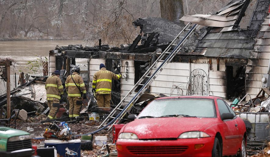 Firefighters remain on the scene following an early morning house fire on Wednesday, Nov. 28, 2018 in Logansport, Ind.  Authorities say four children and two adults are unaccounted for following the house fire.  Cass County Sheriff Randy Pryor told reporters at the scene in Logansport that the six are still believed to be inside the home that burned early Wednesday. (John Terhune/Journal & Courier via AP)