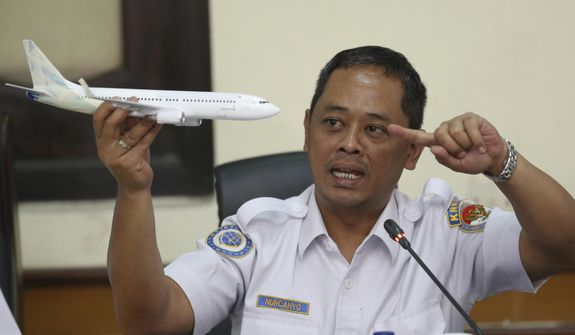 National Transportation Safety Committee investigator Nurcahyo Utomo holds a model of an airplane during a press conference on the committee's preliminary findings on their investigation on the crash of Lion Air flight 610, in Jakarta, Indonesia, Wednesday, Nov. 28, 2018. Black box data collected from their crashed Boeing 737 MAX 8 show Lion Air pilots struggled to maintain control as the aircraft's automatic safety system repeatedly pushed the plane's nose down, according to a preliminary investigation into last month's disaster. (AP Photo/Achmad Ibrahim)