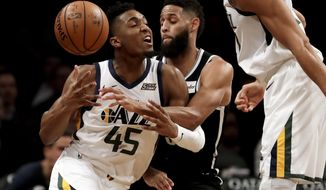 Utah Jazz guard Donovan Mitchell, left, loses the ball while driving against Brooklyn Nets guard Allen Crabbe during the first half of an NBA basketball game, Wednesday, Nov. 28, 2018, in New York. (AP Photo/Julio Cortez)