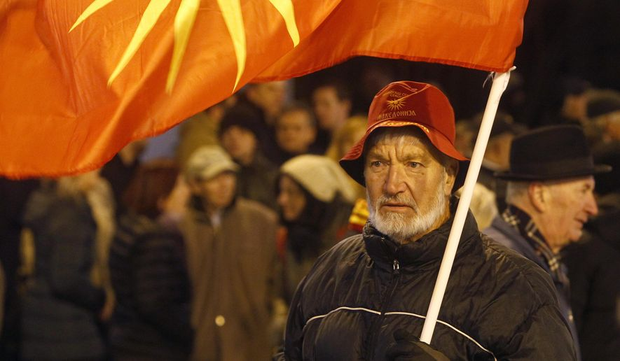 A supporter of the opposition VMRO-DPMNE party waves the old national flag during an anti-government protest march in Skopje, Macedonia, Wednesday, Nov. 28, 2018. Thousands conservative opposition party supporters have marched peacefully late on Wednesday in Macedonia's capital Skopje, protesting leftist government policies, including the deal reached with Greece over the change of the country's name to North Macedonia. (AP Photo/Boris Grdanoski)