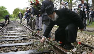 In this Monday May 9, 2015, file photo, a Rabbi puts a rose on the railroad tracks at former concentration camp Westerbork, the Netherlands, remembering more than a hundred thousand Jews who were transported from Westerbork to Nazi death camps. The Dutch national railway company NS says it will set up a commission to investigate how it can pay individual reparations for its role in mass deportations of Jews by Nazi occupiers during World War II. (AP Photo/Peter Dejong)