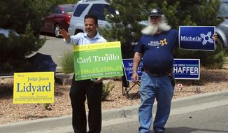 FILE - In this June 5, 2018 file photo, New Mexico state Rep. Carl Trujillo, left, stands with Alan Feldman, a volunteer for the Democratic gubernatorial campaign of Michelle Lujan Grisham, as they greet voters outside a precinct in Santa Fe, N.M. A long-awaited public hearing on sexual harassment accusations against the New Mexico state lawmaker has been canceled after the accuser decided not to testify. A House subcommittee announced Wednesday, Nov. 28, the dismissal of charges against Trujillo. (AP Photo/Morgan Lee)