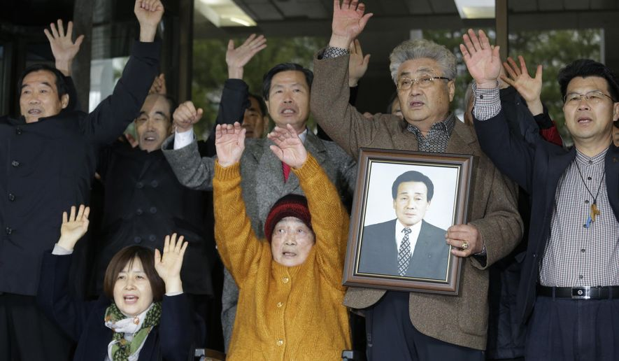 Kim Sung-joo, center bottom, a victim of Japan's forced labor, and their family members and supporters raise their hands in celebration after the Supreme Court's ruling ordering Japan's Mitsubishi Heavy Industries to compensate them in Seoul, South Korea, Thursday, Nov. 29, 2018. South Korea's top court has ordered a Japanese company to compensate 10 Koreans for forced labor during Tokyo's 1910-45 colonial rule of the Korean Peninsula. (AP Photo/Ahn Young-joon)