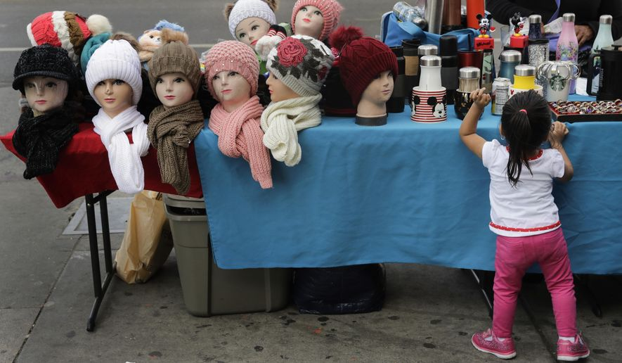 Mannequin heads with beanies are placed on a table as a young girl looks at goods for sale on a sidewalk Tuesday, Nov. 27, 2018, in Los Angeles. They seem to be everywhere on the streets of Los Angeles - pushcarts and tables filled with everything from hot dogs and tamales to toys and tools. Such sales are illegal, although the law is rarely enforced. Now, after a decade of debate and compromise, the Los Angeles City Council will consider an ordinance Wednesday that would grant permits to sidewalk vendors. (AP Photo/Jae C. Hong)