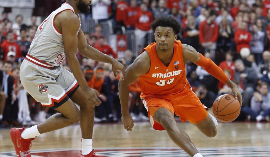 Syracuse's Elijah Hughes, right, drives to the basket against Ohio State's Keyshawn Woods during the first half of an NCAA college basketball game Wednesday, Nov. 28, 2018, in Columbus, Ohio. (AP Photo/Jay LaPrete)
