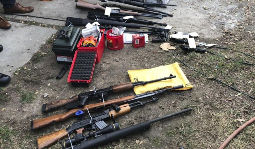 In this photo released Wednesday, Nov. 28, 2018, by the Laguna Beach Police Department are dozens of guns found at a home in Huntington Beach, Calif. A Southern California man arrested on charges of making criminal threats after a dispute over a dove release led police to find guns and Nazi paraphernalia in his home. Laguna Beach police Sgt. Jim Cota says 51-year-old Mitchell Todd was arrested Tuesday night at his home in Huntington Beach.  (Laguna Beach Police Department via AP)