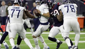 FILE - In this Monday, Nov. 26, 2018, file photo, Tennessee Titans quarterback Marcus Mariota (8) is pressured by Houston Texans outside linebacker Whitney Mercilus (59) during the second half of an NFL football game in Houston. The Titans need to do something to get the offense moving and keep their quarterback from taking so many hits having allowed the most sacks already this season in the NFL. (AP Photo/David J. Phillip, File)