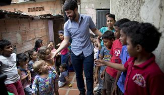 In this Aug. 26, 2018 photo, Roberto Patino greets children at a children's center in the La Vega neighborhood of Caracas, Venezuela. Patino, a rising star in Venezuela's unravelling opposition movement, and other grassroots organizers in their 20s and 30s have been feeding children, encouraging women to become community activists and organizing protests to demand public services like reliable drinking water and electricity. (AP Photo/Ariana Cubillos)