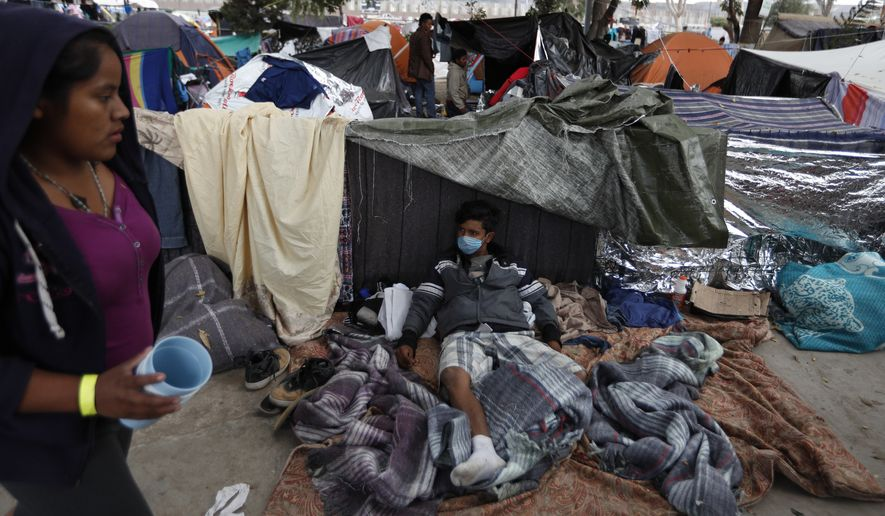 A man wears a surgical mask, used by some migrants to protect against getting or spreading the infections rampant in their close living quarters, inside a sports complex sheltering more than 5,000 Central Americans, in Tijuana, Mexico, Wednesday, Nov. 28, 2018. As Mexico wrestles with what to do with the thousands of people camped out in the border city of Tijuana, President-elect Andres Manuel Lopez Obrador's government signaled Tuesday that it would be willing to house the migrants on Mexican soil while they apply for asylum in the United States, a key demand of U.S. President Donald Trump. (AP Photo/Rebecca Blackwell)