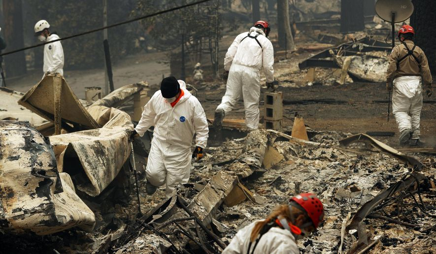 FILE - In this Nov. 13, 2018, file photo, search and rescue workers search for human remains at a trailer park burned out from the Camp fire in Paradise, Calif. About three weeks after a fire leveled a Northern California town, confusion remains and officials continue trying to determine who of the those still listed as unaccounted for are really missing, which is not easy. Some families meet frustration in their search while others who escaped the inferno are surprised to find themselves listed as missing. (AP Photo/John Locher, File)