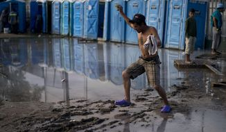 A migrant, part of the migrant caravan, try to cross a flooded area after bathing at a sports complex where more than 5,000 Central American migrants are sheltering in Tijuana, Mexico, Wednesday, Nov. 28, 2018. As Mexico wrestles with what to do with the thousands of people camped out in the border city of Tijuana, President-elect Andres Manuel Lopez Obrador's government signaled that it would be willing to house the migrants on Mexican soil while they apply for asylum in the United States, a key demand of U.S. President Donald Trump. (AP Photo/Ramon Espinosa)