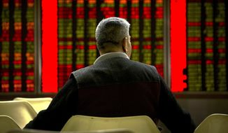 A Chinese investor monitors stock prices at a brokerage house in Beijing, Thursday, Nov. 29, 2018. Asian stocks followed Wall Street higher on Thursday after U.S. Federal Reserve Chairman Jerome Powell suggested the pace of interest rate increases might slow.(AP Photo/Mark Schiefelbein)