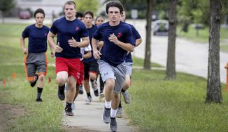 In this Sept. 6, 2018 photo, Marine Corp recruits take part in a 1.5 mile run in Champaign, Ill. Future soldiers work out at the recruiting station, getting a taste of what boot camp will be like, preparing for the upcoming physical rigors. (Rick Danzl/The News-Gazette via AP)