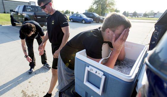 In this Sept. 20, 2018 photo, Henry Johnson, right, puts his arms in a cooler after running a mile in the 105-degree heat index with Staff Sgt. Brandon Howell, center, during a weekly session of the U.S. Army's Future Soldier Training behind the Armed Forces Career Center at Parkland Plaza in Champaign, Ill. Twenty or so future soldiers work out at the recruiting station, getting a taste of what boot camp will be like, preparing for the upcoming physical rigors. (Stephen Haas/The News-Gazette via AP)