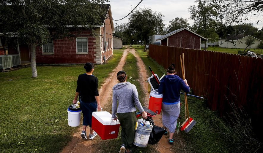 Amish volunteers with the Mennonite Disaster Service carry cleaning supplies down a road after finishing building a home for a man who lost his house to Hurricane Harvey Tuesday, Nov. 13, 2018, in Bloomington, Texas.(Michael Ciaglo/Houston Chronicle via AP)