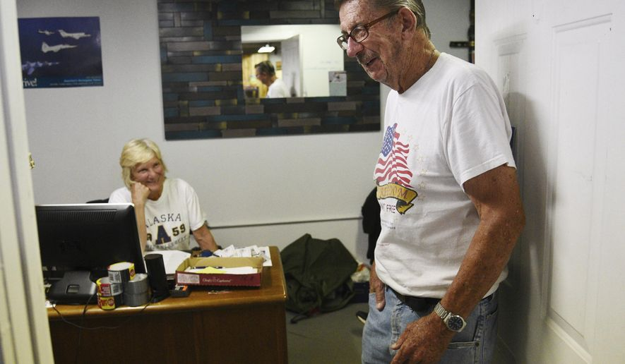 """In this Aug. 2, 2018 photo, Russ """"Pops"""" McCann brings a smile to the face of director Mary Carmody at the Midwest Veterans Closet in North Chicago, Ill. McCann has spent many weekdays for about the past four years volunteering at the Midwest Veterans Closet doing wherever needed. He has found a renewed sense of purpose at the nonprofit, which provides veterans and their families with clothing, household items, shoes, boots and other basic needs, as well as housing and employment assistance, at no cost. (Paul Valade/Daily Herald, via AP)"""