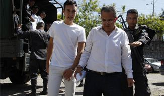 Elvin Rapalo, left, and Sergio Rodriguez, accused in the murder of Honduran indigenous and environmental rights activist Berta Caceres, are led in handcuffs to court by police in Tegucigalpa, Honduras, Thursday, Nov. 29, 2018. Rapalo, Rodriguez and other five accused were found guilty by a court and will be sentenced on January 2019. (AP Photo/Fernando Antonio)