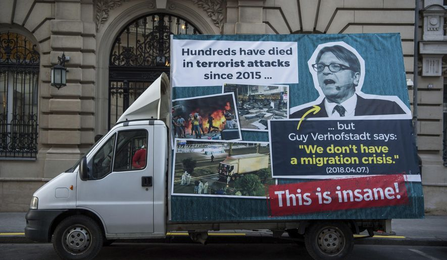 A huge photo of the leader of the Alliance of Liberals and Democrats for Europe in the European Parliament Guy Verhofstadt is seen on the billboard of a van parking in front of the Prime Minister's Office after it was introduced by government spokesman Zoltan Kovacs during his press conference in Budapest, Hungary, Wednesday, Nov. 28. 2018. The placard says 'Hundreds have died in terrorist attacks since 2015, but Guy Verhofstadt says: 'We don't have a migration crisis. (07/04/2018)' 'This is insame!' (Zoltan Balogh/MTI via AP)