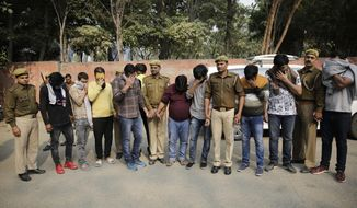 Alleged fraudsters are presented before media at a police station in Noida, a suburb of New Delhi, India, Thursday, Nov. 29, 2018. Indian police said Thursday that they have arrested nearly two dozen people on suspicion of defrauding people around the world by sending fake pop-up messages warning them that their computers were infected with a virus and offering to rectify the problem at a price. (AP Photo/Altaf Qadri)