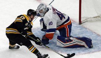 Boston Bruins center Ryan Donato (17) scores against New York Islanders goaltender Robin Lehner (40) during a shootout in an NHL hockey game, Thursday, Nov. 29, 2018, in Boston. (AP Photo/Elise Amendola)