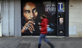 A woman walks past a mural depicting reggae music icon Bob Marley painted on the rolling shutter of a Tobacconist shop in Rome, Thursday, Nov. 28, 2018. (AP Photo/Gregorio Borgia)
