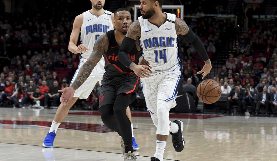 Orlando Magic guard D.J. Augustin, right, passes the ball behind his back to guard Evan Fournier, back left, as Portland Trail Blazers guard Damian Lillard, center, defends during the first half of an NBA basketball game in Portland, Ore., Wednesday, Nov. 28, 2018. (AP Photo/Steve Dykes)