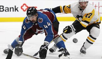 Colorado Avalanche defenseman Mark Barberio, left, is checked by Pittsburgh Penguins right wing Bryan Rust while they pursue a puck in the second period of an NHL hockey game Wednesday, Nov. 28, 2018, in Denver. (AP Photo/David Zalubowski)