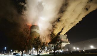 Clouds of smoke over Europe's largest lignite power plant in Betchatow, central Poland, on Wednesday, Nov. 28, 2018.  A group of Greenpeace environment activists have climbed its 180-meter smokestack to spur participants in next week's global climate summit in Poland into taking decisions on limiting the use of coal.(AP Photo/Czarek Sokolowski)