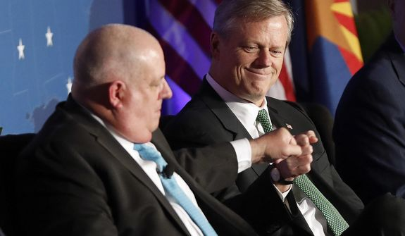 In this file photo, Maryland Gov. Larry Hogan, left, knuckles Massachusetts Gov. Charlie Baker, right, during the Republican Governors Association annual conference, Wednesday, Nov. 28, 2018, in Scottsdale, Ariz. Mr. Baker and Mr. Hogan were found by a Morning Consult survey to be the top two most popular governors in the United States in the second quarter of 2019, going off their approval ratings. (AP Photo/Matt York) **FILE**