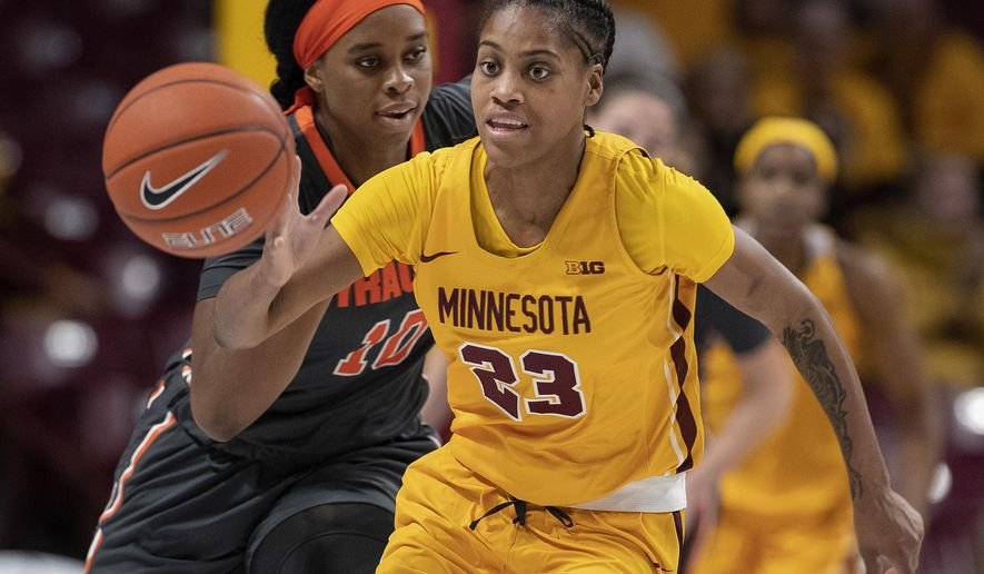 Minnesota's Kenisha Bell (23) brings the ball up as Syracuse's Marie-Paule Foppossi trails during the first half of an NCAA college basketball game Thursday, Nov. 29, 2018, in Minneapolis. (Carlos Gonzalez/Star Tribune via AP)