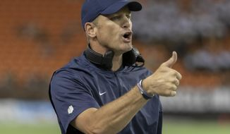 FILE - In this Nov. 3, 2018, file photo, Utah State coach Matt Wells gestures to officials during the first half of the team's NCAA college football game against Hawaii in Honolulu. Texas Tech has hired Wells as its new football coach after he was part of an impressive turnaround at Utah State, his alma mater. The hiring was announced by Texas Tech on Thursday night, Nov. 29. (AP Photo/Eugene Tanner, File)